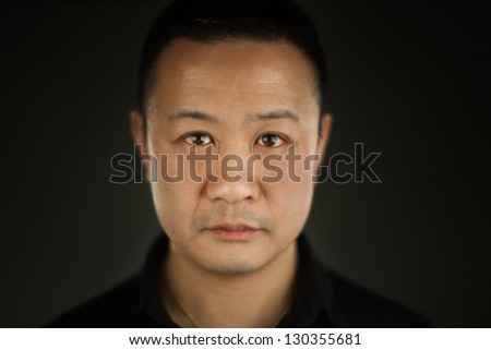 A shallow depth of field close up portrait of a young Asian man - stock photo