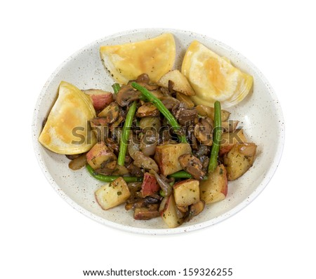 A shallow serving dish with cooked pierogies, green beans, red potatoes, mushrooms and onions on a white background. - stock photo