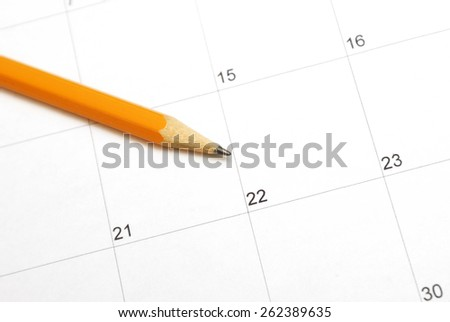 A sharpened pencil rests on a calendar for use in planning the days in the month. - stock photo