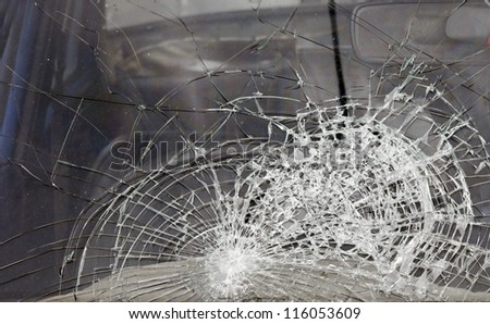 A shattered glass windscreen of a car.