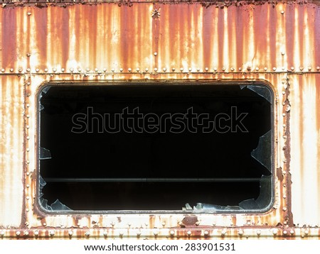 A shattered old train window surrounded by rust and decay. - stock photo