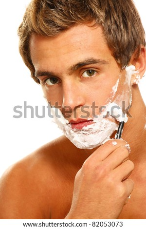 A shaving handsome man, close-up, isolated on white - stock photo