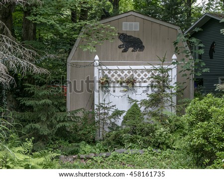 A shed with a silhouette of a bear, being overgrown by grass and bush.