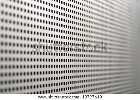 A sheet of aluminum with square perforations receding in shallow DOF - stock photo