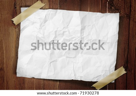 A sheet of crumpled paper is taped on a wooden wall with a path.