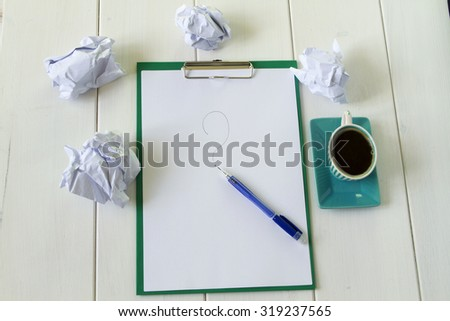 a sheet of paper on a green plate, crumpled paper, a question mark written in pencil, a mug of coffee, all in a white wooden background - stock photo