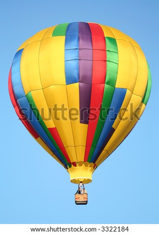 A Shiny Colorful Hot Air Balloon in a Clear Blue Sky - stock photo