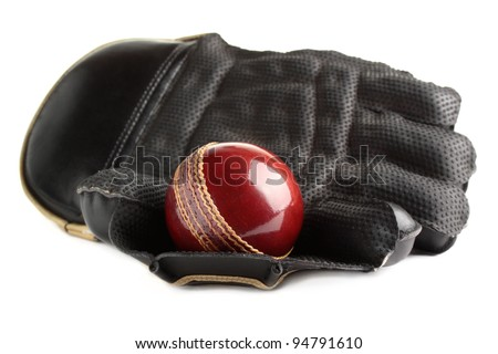 A shiny, new test match cricket ball in a wicket keeping glove. Isolated on a white background. - stock photo