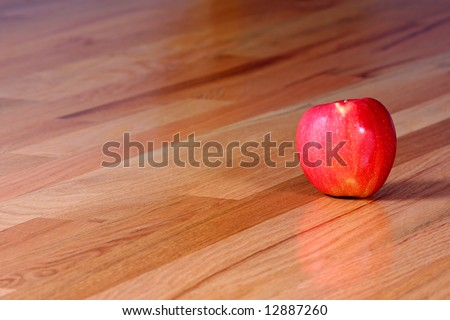 A shiny red apple on a hardwood floor. - stock photo