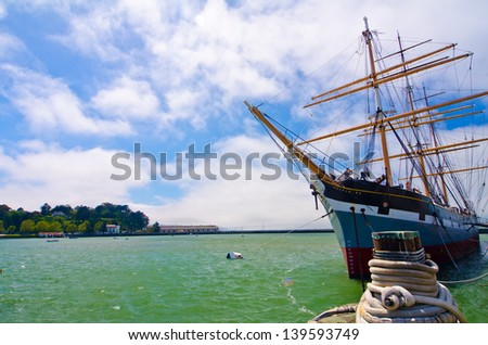 A ship docked at Fisherman's Wharf with the Golden Gate Bridge in the background. - stock photo