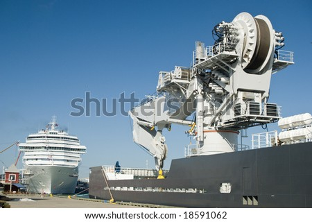 A ship fitted with a massive crane with a cruise ship in the background. - stock photo