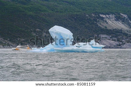 a ship is navegating in argentino lake, where are floating icebergs which have broken from the glacier Perito Moreno - stock photo