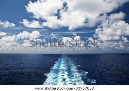 A ship's propeller wake over the open blue sea - stock photo