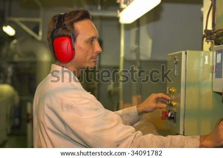 A shipping engineer manages automation panel devices - stock photo