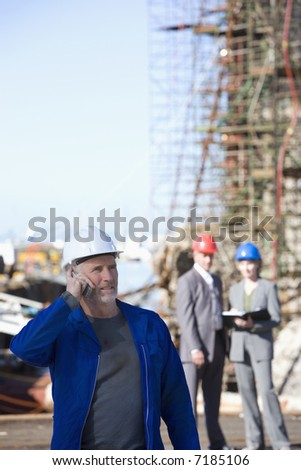 A shipping engineer on his cellphone in front of an oil platform in the harbor