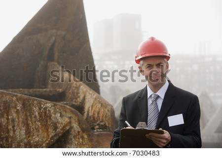 A shipping inspection engineer taking notes in front of a large rusted anchor in the early morning fog