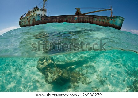 A shipwreck is grounded in extremely shallow water near the Turks & Caicos Islands.  Shipwrecks often act as artificial reefs, attracting invertebrates and fish. - stock photo
