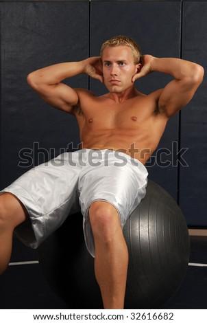 A shirtless muscular man doing sit ups - stock photo