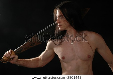 A shirtless warrior brandishing a sword - stock photo