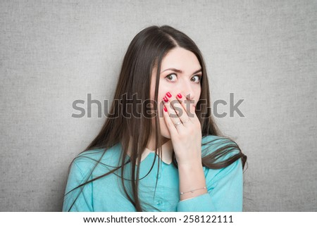 A shocked and frightened woman covering her mouth in surprise and disbelief. Isolated - stock photo