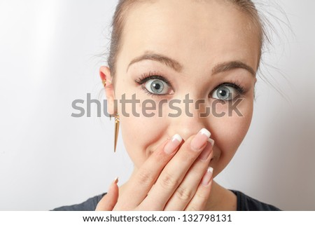 A shocked frightened young girl covering his mouth with his hand and staring wide eyed at the camera. Shot on white background. - stock photo