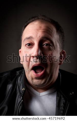 A shocked or surprised man with a goofy look on his face. - stock photo
