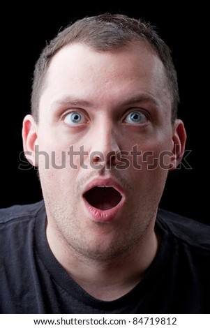 A shocked or surprised middle aged man over a dark background. - stock photo
