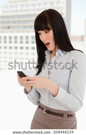 A shocked woman reading a text message from her phone while at work - stock photo