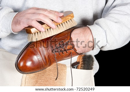 A shoeshine man polishing a leather dress shoe - stock photo