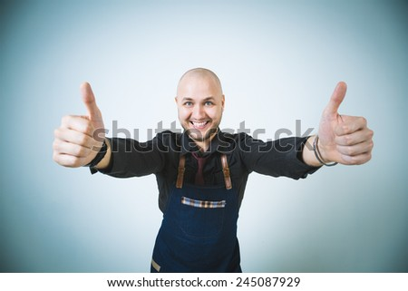A shoot of young caucasian men in apron as a barmen. Showing the sign good, thumbs up. - stock photo
