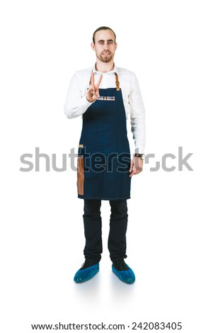 A shoot of young caucasian men in apron as a barmen. Showing the sign victory, two fingers up, - stock photo