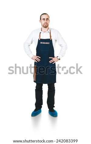 A shoot of young caucasian men in apron as a barmen with arms akimbo. Isolated against white background.