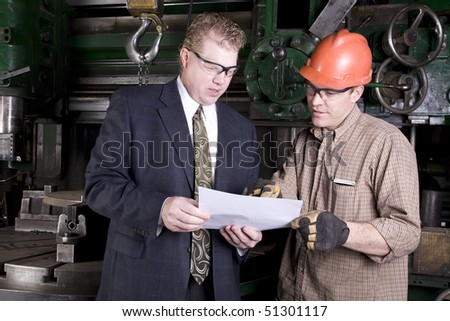 A shop worker showing his boss something on his blue print of a part.