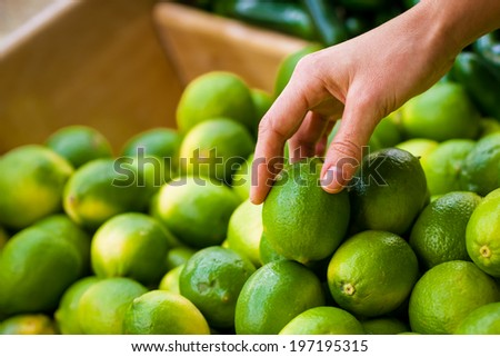 A shopper picks a green lime from a box - stock photo