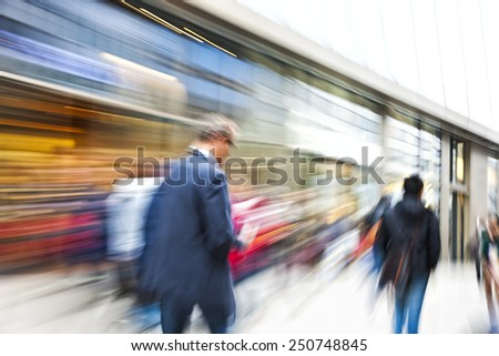 A shopper walking past a store window - stock photo