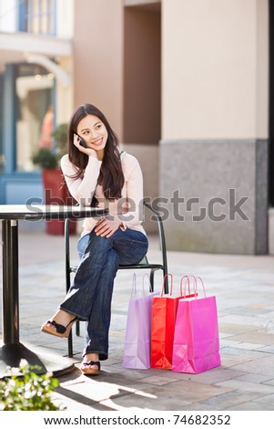 A shopping asian woman talking on her phone - stock photo