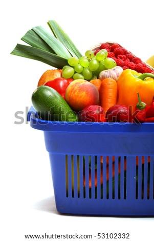 A shopping basket full of fresh produce on white. - stock photo