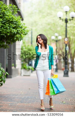 A shopping black woman talking on her phone - stock photo