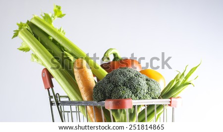 a shopping cart filled with vegetables on a white background
