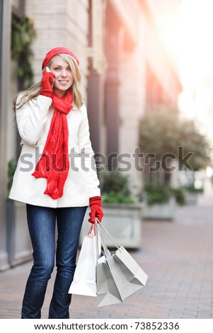 A shopping caucasian woman carrying shopping bags and talking on the phone at an outdoor shopping mall - stock photo
