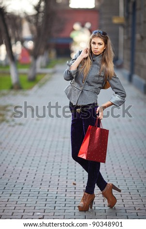 A shopping woman carrying shopping bags outdoor - stock photo