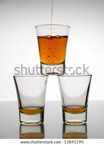 A shot being poured over other two almost empty shots. - stock photo