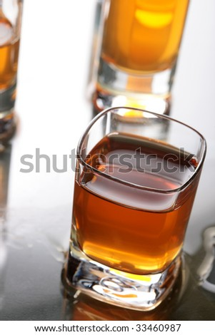 A shot glass full of whiskey with other shot glasses in the background. Shallow DOF. - stock photo
