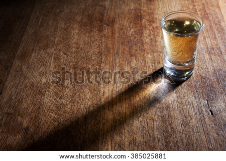 A shot glass of Brazilian gold cachaca isolated on rustic wooden background with beautiful shadow.