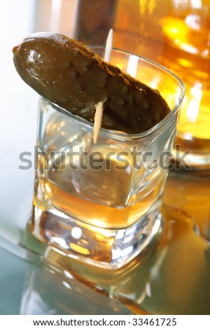 A shot glass of whiskey partially full with a pickle on a tooth pick. - stock photo