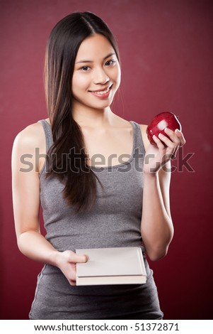 A shot of a beautiful asian college student carrying a book and an apple