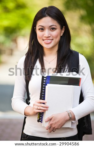 A shot of a beautiful asian college student on campus - stock photo