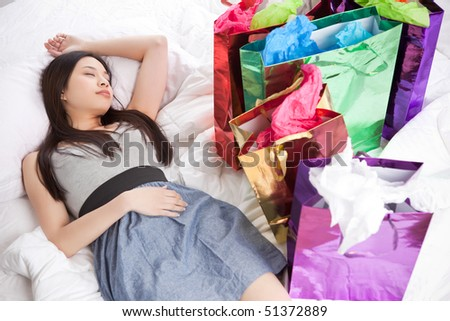 A shot of a beautiful asian girl sleeping on the bed after shopping