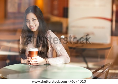 A shot of a beautiful asian woman drinking coffee in a cafe (shot through window) - stock photo