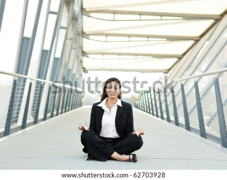 A shot of a beautiful black businesswoman meditating - stock photo